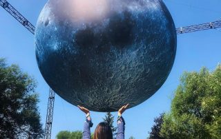 Girl holding up a model of the moon